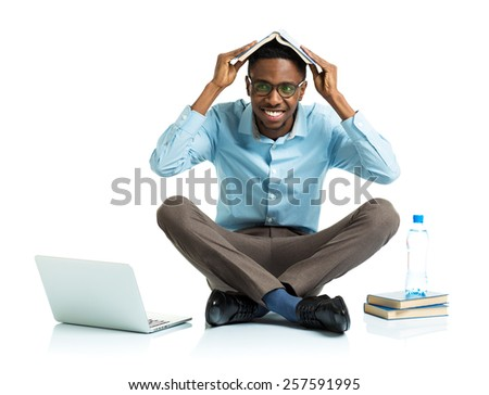 Happy african american college student with laptop, books and bottle of water sitting on white background - stock photo