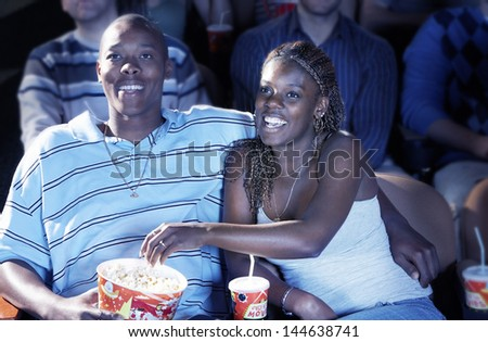 Happy African American couple eating popcorn while watching movie In theatre - stock photo