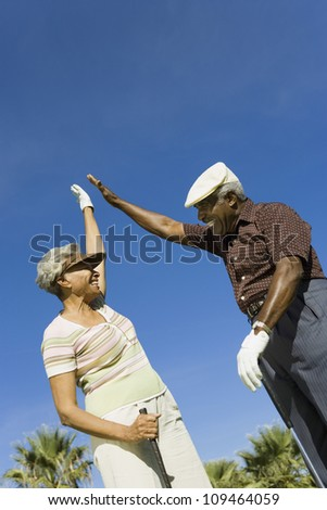 Happy African American couple giving high-five on golf course