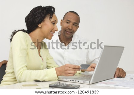 Happy African American couple paying bills online at home - stock photo