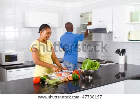 happy african american couple preparing food in kitchen