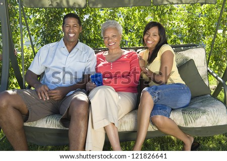 Happy African American couple sitting with mother on swing in lawn - stock photo