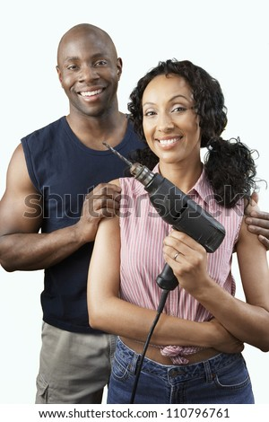 Happy African American couple with woman holding drill - stock photo