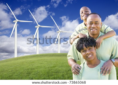 Happy African American Family and Wind Turbine with Dramatic Sky and Clouds. - stock photo