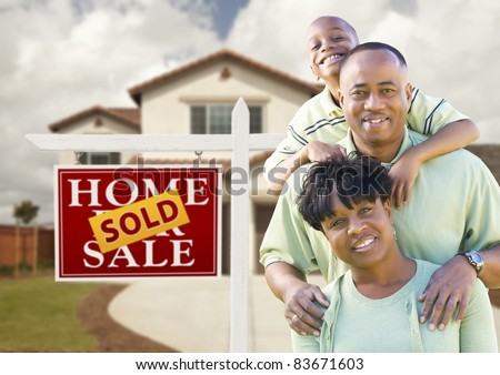 Happy African American Family in Front of New House and Sold Real Estate Sign. - stock photo