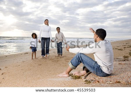 Happy African-American family of four on beach, father waiting with open arms - stock photo