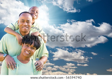 Happy African American Family Over Blue Sky, Sun Rays and Clouds.