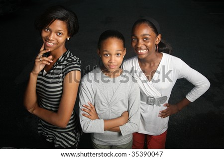 Happy African American family. Three teenage sisters together looking at camera, smiling. - stock photo