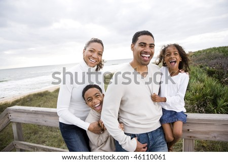 Happy African-American family with two children laughing at beach