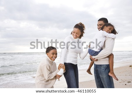 Happy African-American family with two children on beach - stock photo