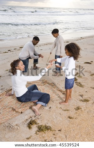 Happy African-American family with two children playing together on beach - stock photo