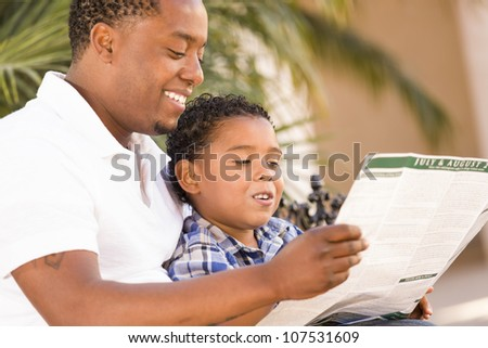 Happy African American Father and Mixed Race Son Having Fun Reading Park Brochure Outside. - stock photo