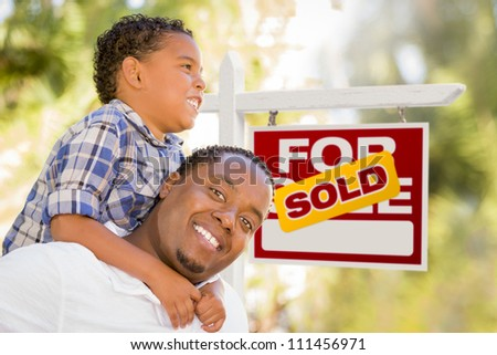 Happy African American Father and Mixed Race Son in Front of Sold Real Estate Sign. - stock photo