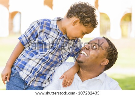 Happy African American Father and Mixed Race Son Playing in the Park. - stock photo