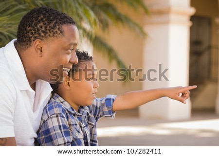 Happy African American Father and Mixed Race Son Pointing in the Park. - stock photo