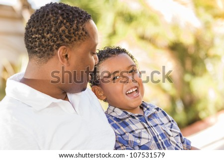 Happy African American Father and Mixed Race Son Talking in the Park. - stock photo