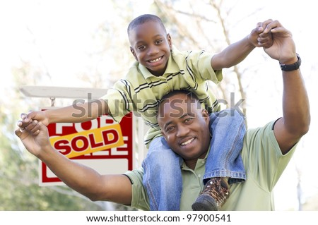 Happy African American Father and Son in Front of Sold Real Estate Sign. - stock photo