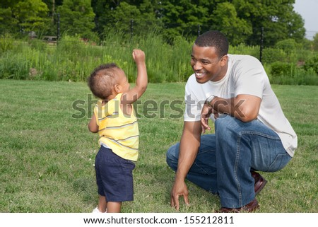 Happy African American Father and Son Playing Outdoor Park in Summer - stock photo