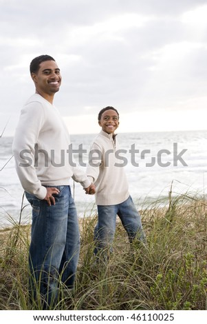 Happy African-American father and son walking together along sand dunes and grass at beach - stock photo