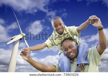 Happy African American Father and Son with Wind Turbine Over Blue Sky. - stock photo