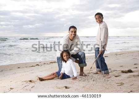 Happy African-American father and two children together on beach - stock photo
