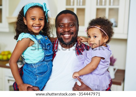 Happy African-American father and two cute girls looking at camera
