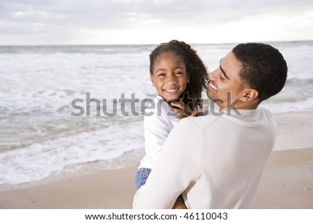 Happy African-American father holding six year old daughter at beach - stock photo