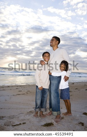 Happy African-American father,  ten year old son and six year old daughter standing on beach - stock photo