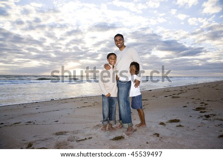 Happy African-American father,  ten year old son and six year old daughter standing on beach