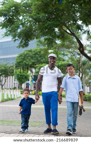 Happy African-American father with his two sons walking in the park - stock photo