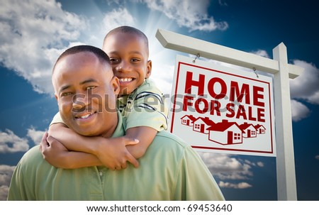 Happy African American Father with Son In Front of Home For Sale Real Estate Sign and Sky.