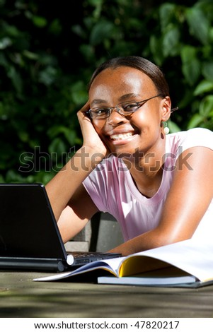 happy african american female student studying computer outdoors - stock photo