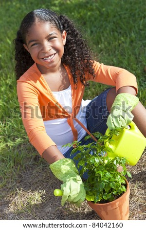 Happy African American girl child gardening planting flowers and watering a flower pot