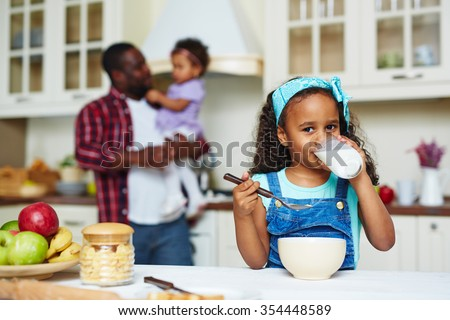 Happy African-American girl looking at camera while drinking milk - stock photo