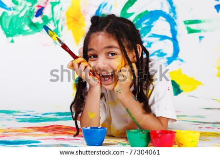 Happy african american girl lying on the floor with a paintbrush