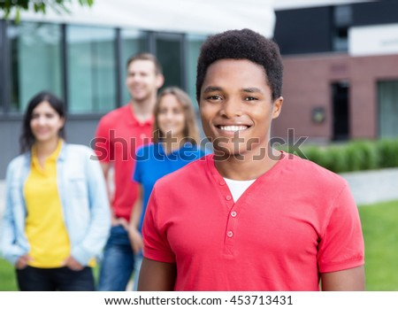 Happy african american guy and multi ethnic friends outdoor - stock photo