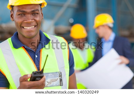 happy african american industrial worker with walkie talkie on site with colleagues - stock photo