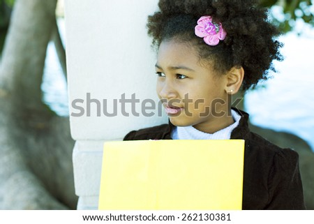 Happy african american little girl with book - stock photo