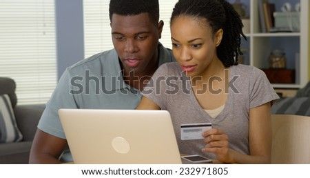 Happy African American man and woman making online purchase with credit card - stock photo