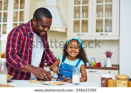 Happy African-American man helping his daughter make sandwich - stock photo