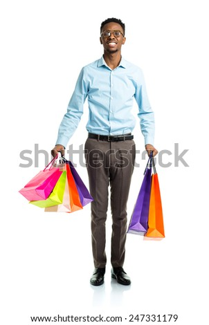 Happy african american man holding shopping bags on white background. Christmas and holidays concept - stock photo