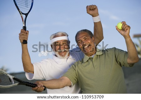 Happy African American man with a friend playing tennis - stock photo