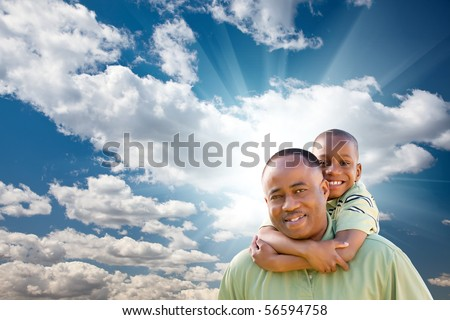 Happy African American Man with Child Over Blue Sky, Clouds and Sun Rays.