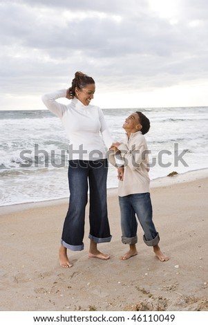 Happy African-American mother and ten year old son standing together on beach