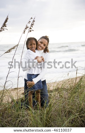 Happy African-American mother hugging six year old daughter at beach - stock photo