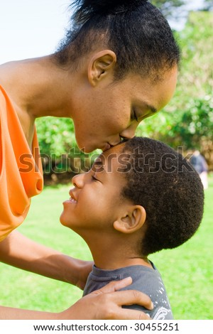 happy african american mother kissing  son - stock photo