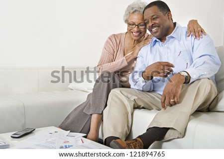 Happy African American senior couple sitting on sofa at home - stock photo