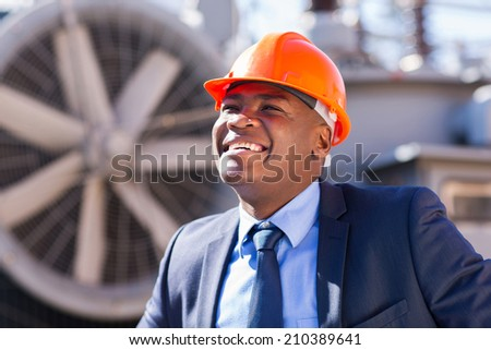 happy african american technical manager standing in electricity power plant