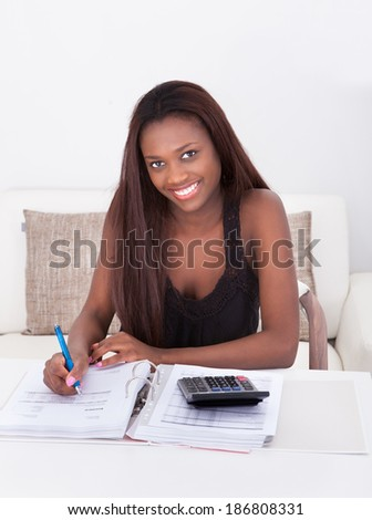 Happy African American woman calculating finance at home - stock photo