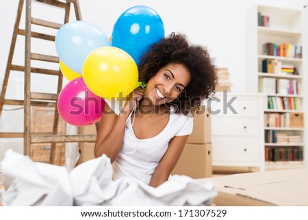 Happy African American Woman celebrating her move to a new house kneeling on the floor in the living room surrounded by crumpled paper holding colorful party balloons - stock photo